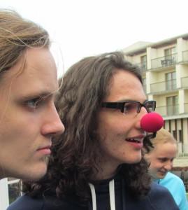 Drei Personen, Blick nach rechts, in der Mitte mit roter Clowns-Nase
