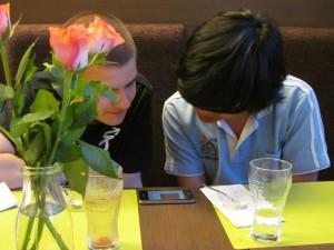 Zwei Contestants beugen sich über ein Mobiltelefon, der vorherige Blog-Eintrag geöffnet.