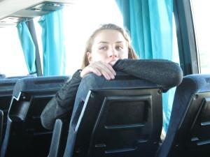 Agnieszka schaut über einen Sitz im Bus.