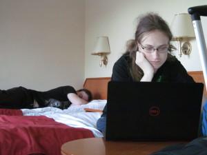 Julian starrt auf seinen Laptop, während Julian schon eingeschlafen ist.