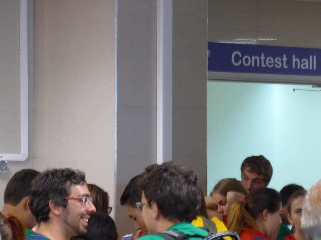 A crowd in front of the contest hall (labelled as such by a sign)