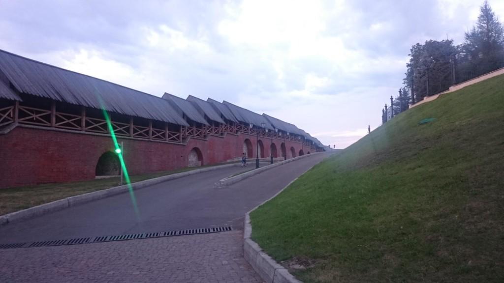 Mauer des Kremlins von Kasan, davor eine Straße und eine Wiese. Ein grünes Ampellicht