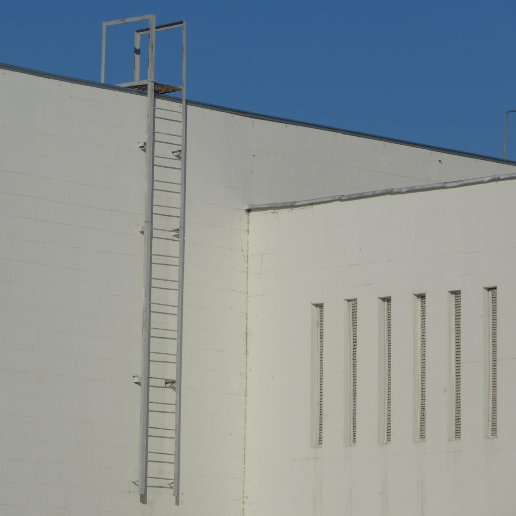 Eine Leiter und sehr schmale Fenster an einer weißen Fassade