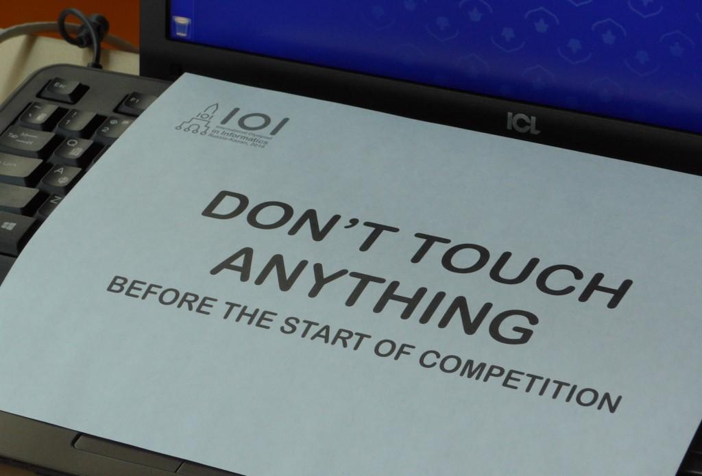 """Papier mit der Aufschrift """"DON'T TOUCH ANYTHING BEFORE THE START OF COMPETITION"""" auf einem Laptop"""